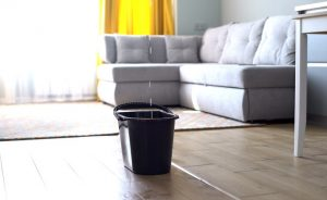 Gray bucket sitting in the middle of a home living room with water dropping into it from the ceiling.