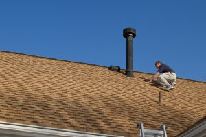 Home Inspector, on the roof, examines a roof gas vent.