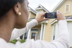 Young woman real estate agent taking a picture of a home on her mobile phone.