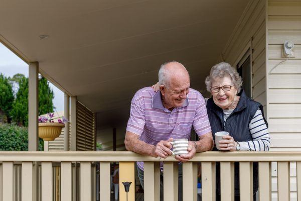Older couple drinking coffee on their front porch