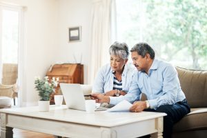 Senior couple using a laptop together at home.