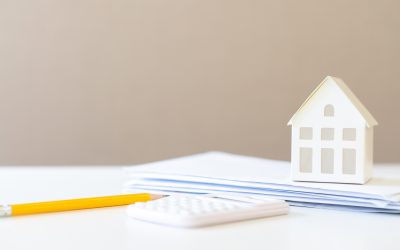 Pencil, calculator, and stack of paper on a table with a small house model sitting on top of the papers.