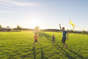 Dad flying a kite with his two small children while running through a green field.