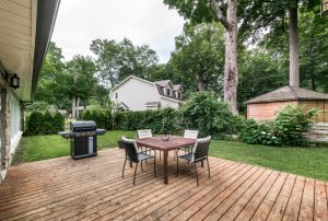 Exterior view of a backyard in neighborhood with a large deck, outdoor dining set and BBQ.
