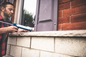Man applying caulking around window frame
