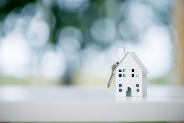 A miniature model house is sitting on a desk. A house key is dangling from the roof. The scene symbolizes purchasing a new house.