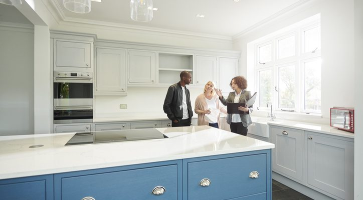 A couple talking with a real estate agent in a new home they're touring.