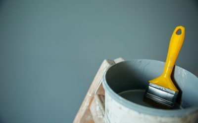 Bucket of blue wall paint with a yellow paintbrush handle sticking out of it.