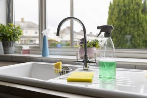 A selection of cleaning products on top of a kitchen sink.
