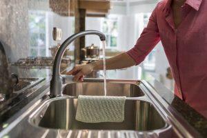 A woman letting the kichen faucet run.