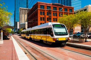 A light rail train at a stop in a city or metropolitan area.