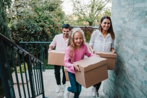 Smiling family carrying boxes into their new house.