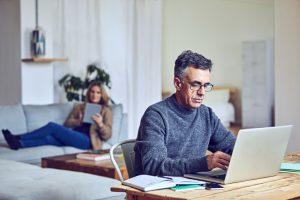 A senior man using a laptop at home.
